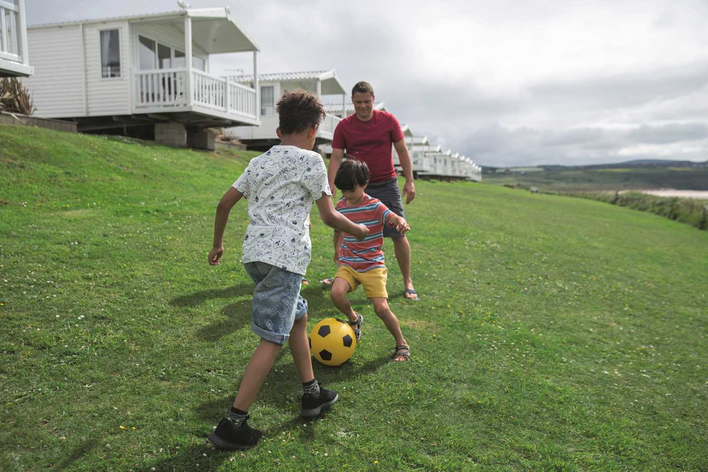 a boy playing football with his family