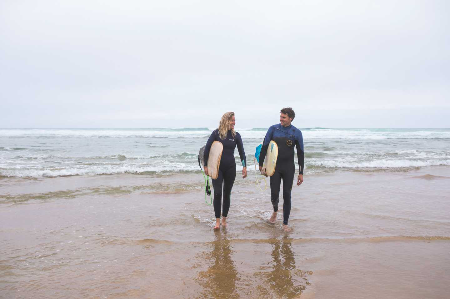 Couple enjoying surfing at Perran Sands Beach
