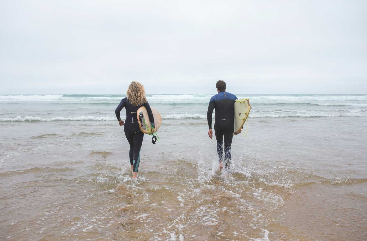 A couple surfing at Perran Sands