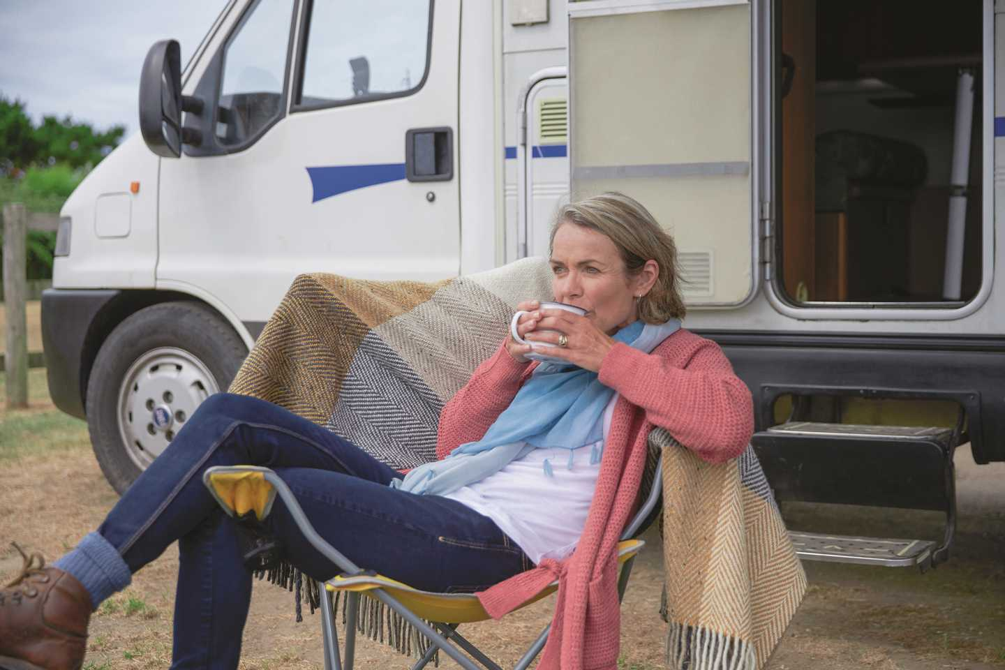 A woman relaxing with a cup of tea outside her tourer