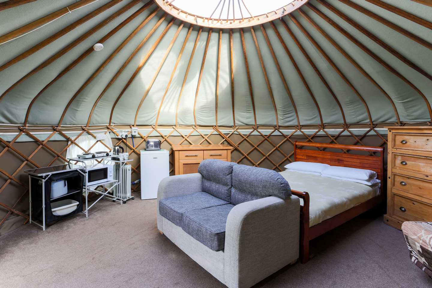 A Yurt with a double bed, sofa and kitchen appliances