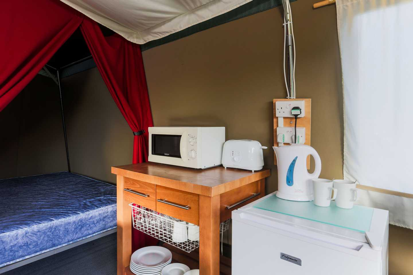 Kitchen area with appliances in a Super Tent at Perran Sands