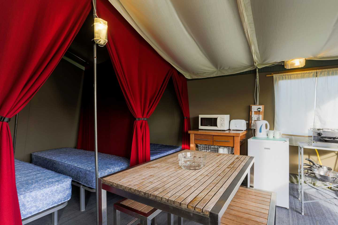 The sleeping area and dining area of a Super Tent at Perran Sands