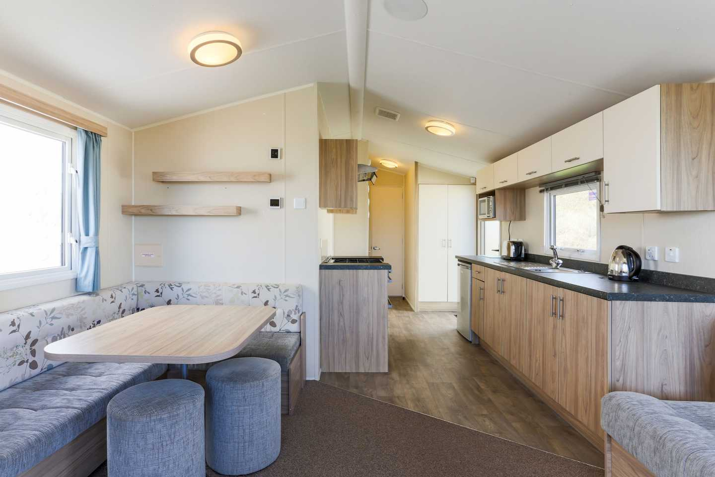 The kitchen and dining area in a Deluxe caravan