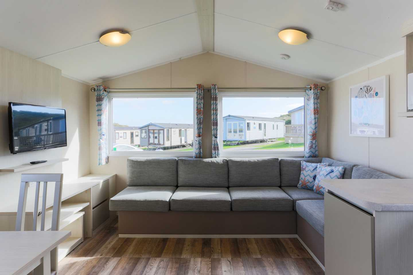 An Adapted caravan with dining area, TV and sofa