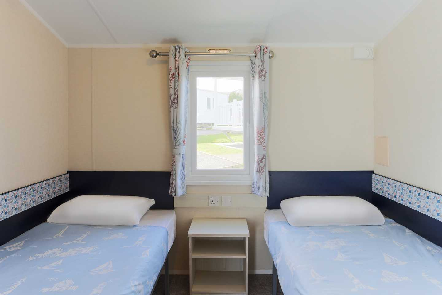 An Adapted caravan twin bedroom with two beds and drawer unit