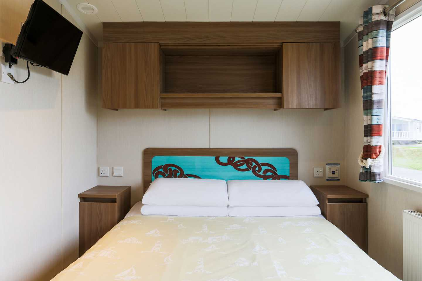A Prestige master bedroom with double bed, overhead storage and bedside cabinets