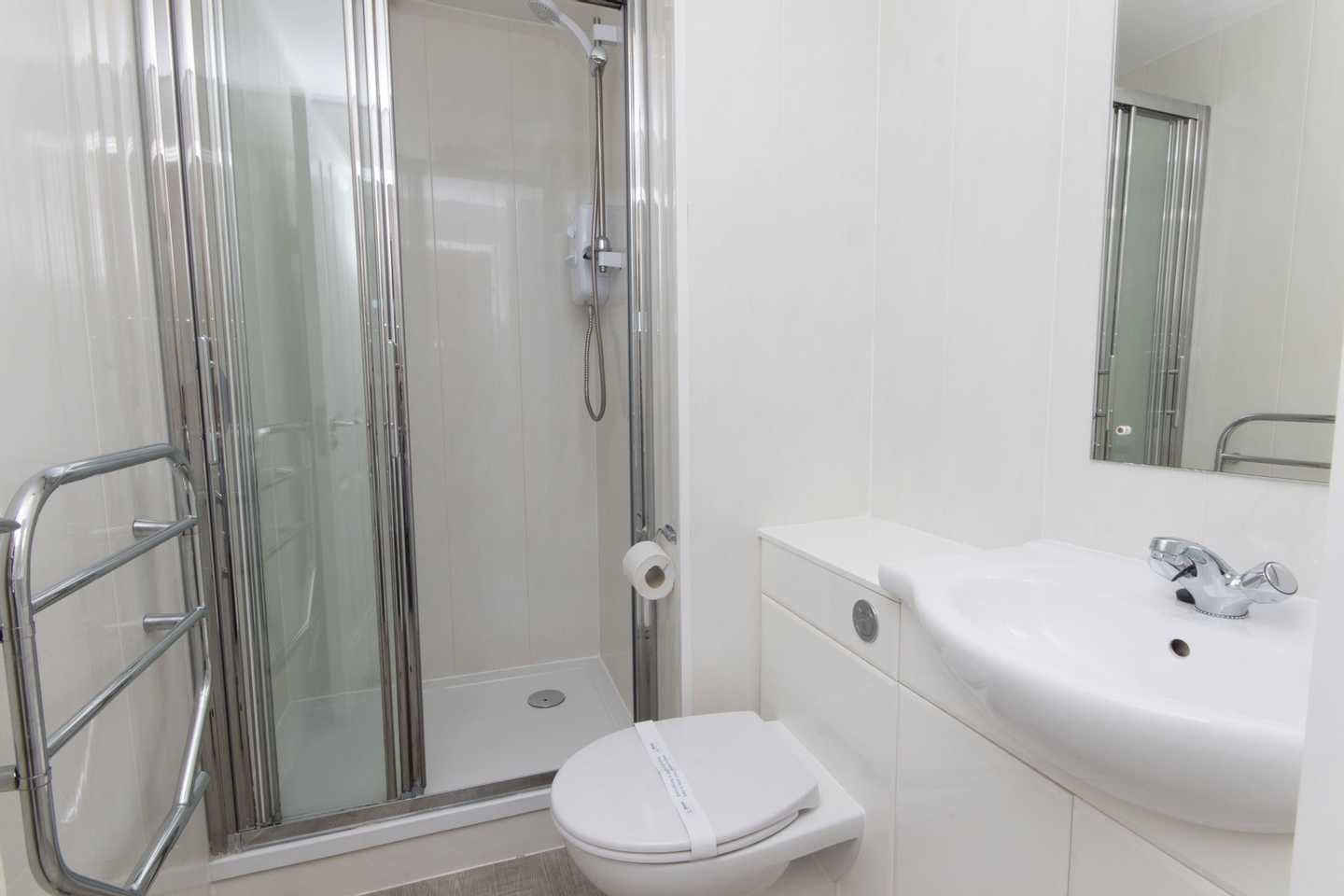 A Comfort with veranda bathroom with shower, toilet, sink and mirror