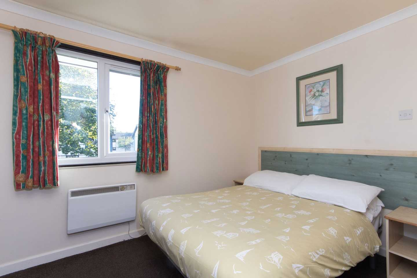 A Comfort apartment master bedroom with double bed, two bedside tables with lamps and a radiator
