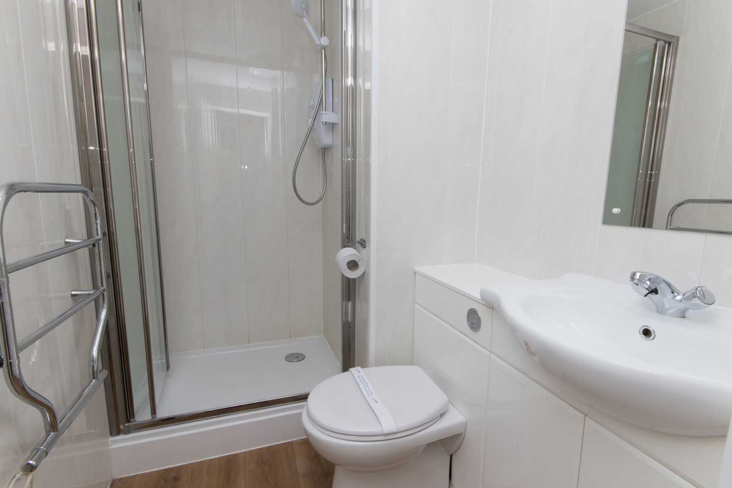A Comfort apartment bathroom with toilet, sink, shower and mirror