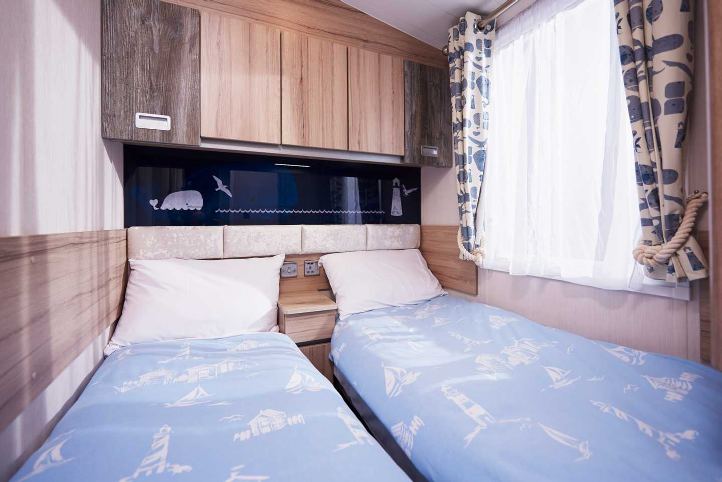 A Platinum caravan twin bedroom with 2 single beds and a bedside cabinet