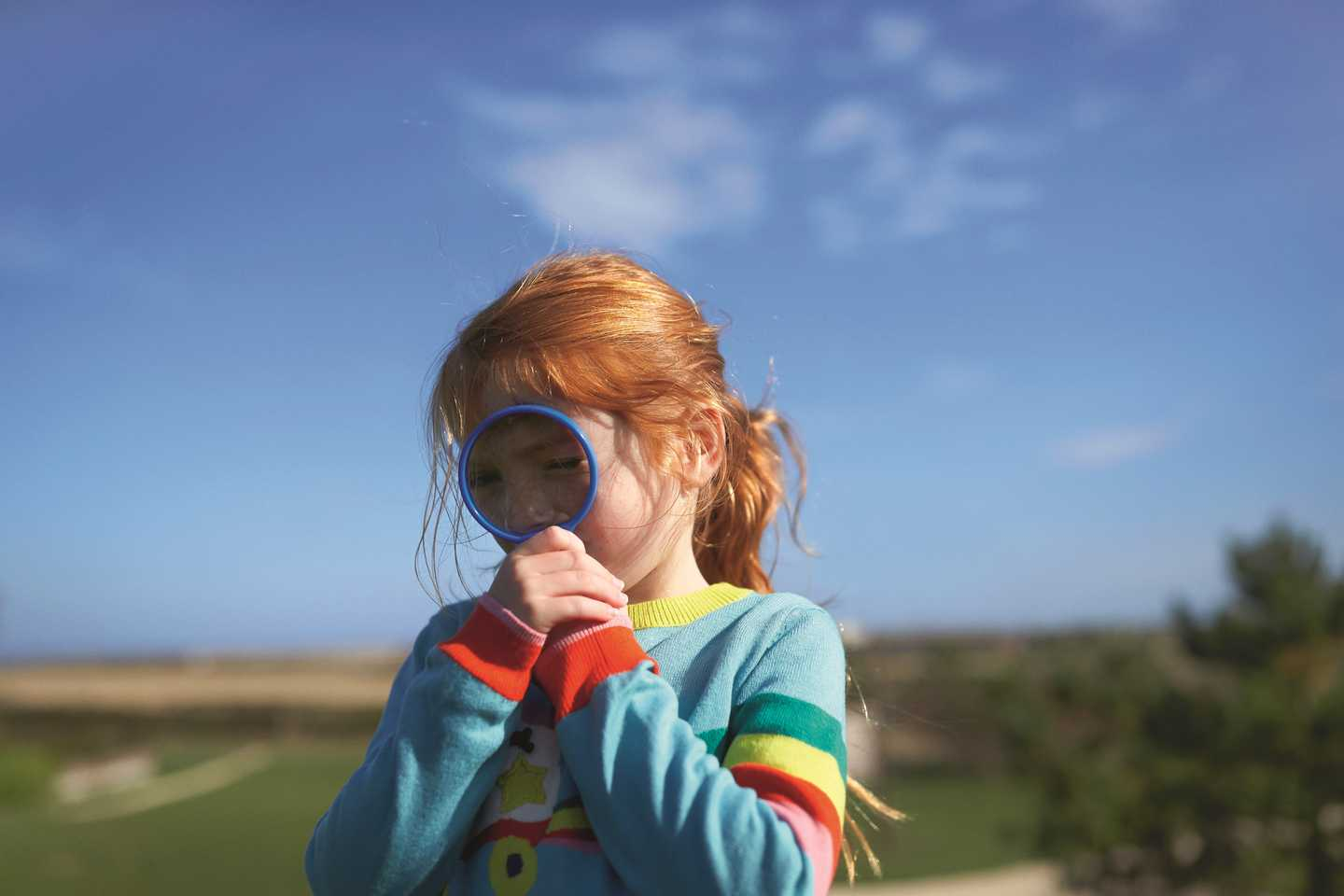A girl looking at bugs with a magnifying glass