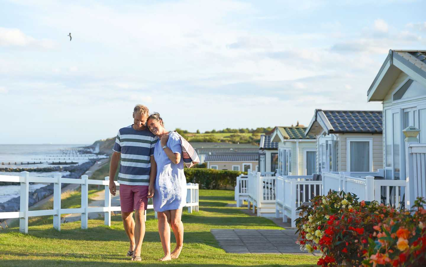 Couple walking beside the holiday homes at Hopton
