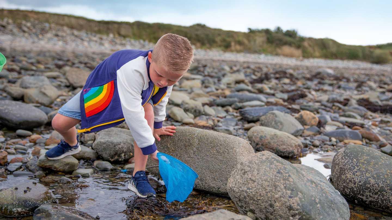 A little boy on the beach at Hafan y Môr