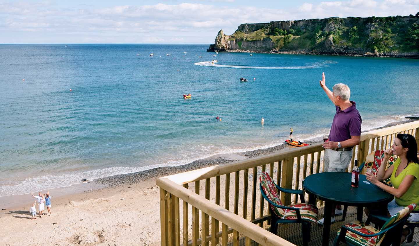 Owners waving to their friends from their veranda at Lydstep Beach