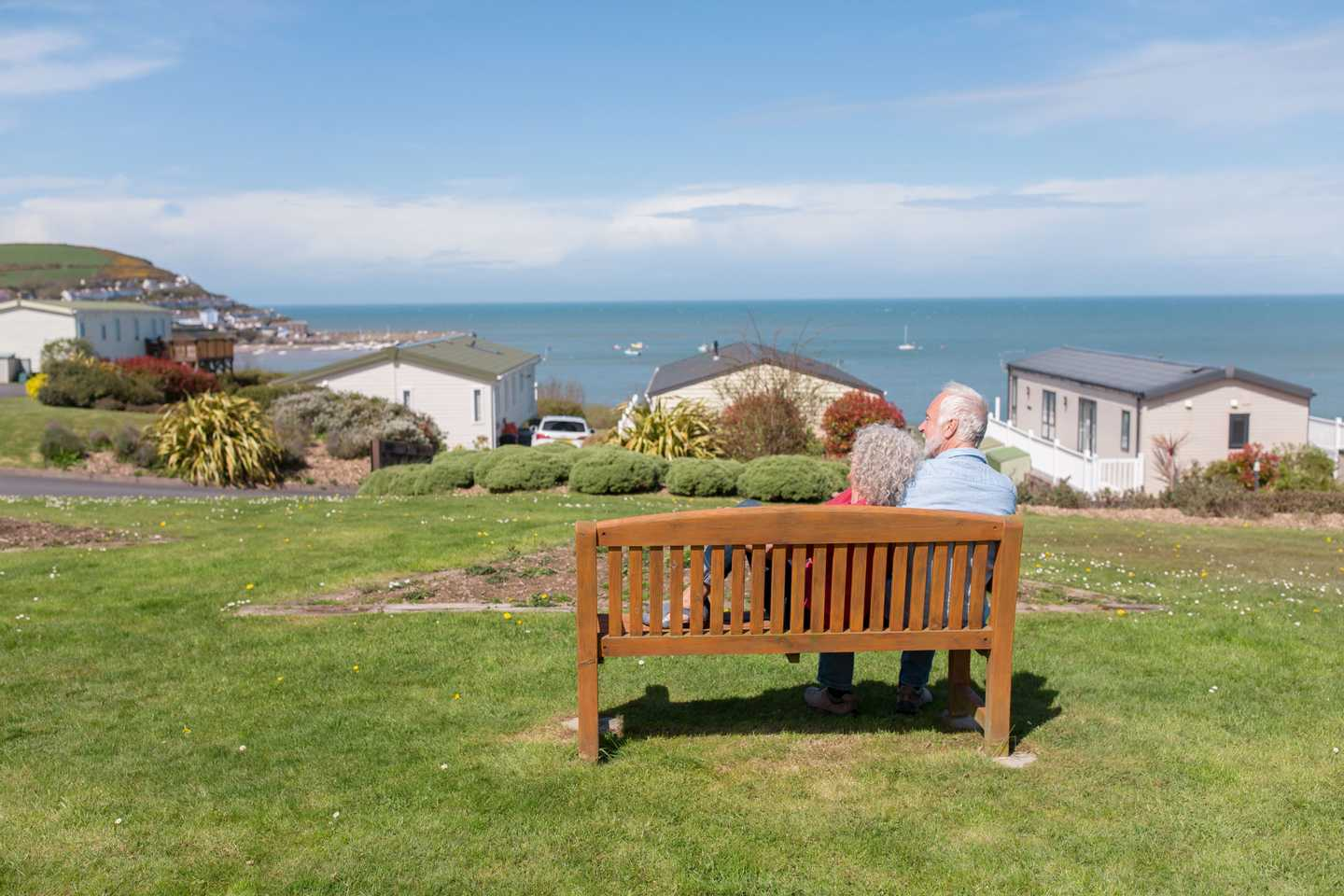 Owners sitting on a bench overlooking the sea at Quay West