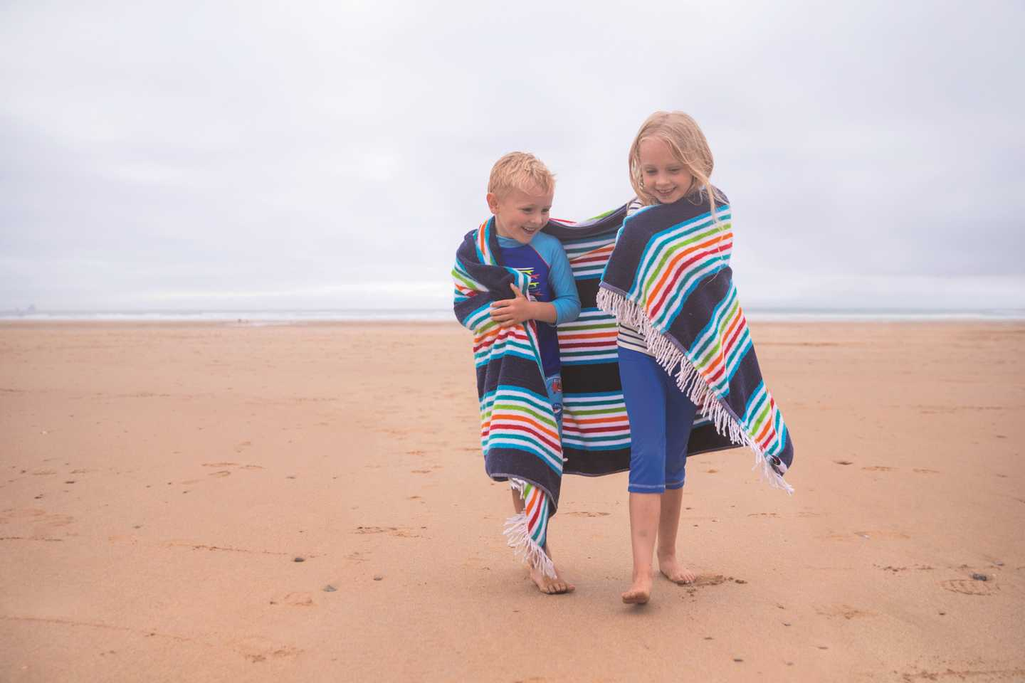 Children wrapped in a towel walking along the beach
