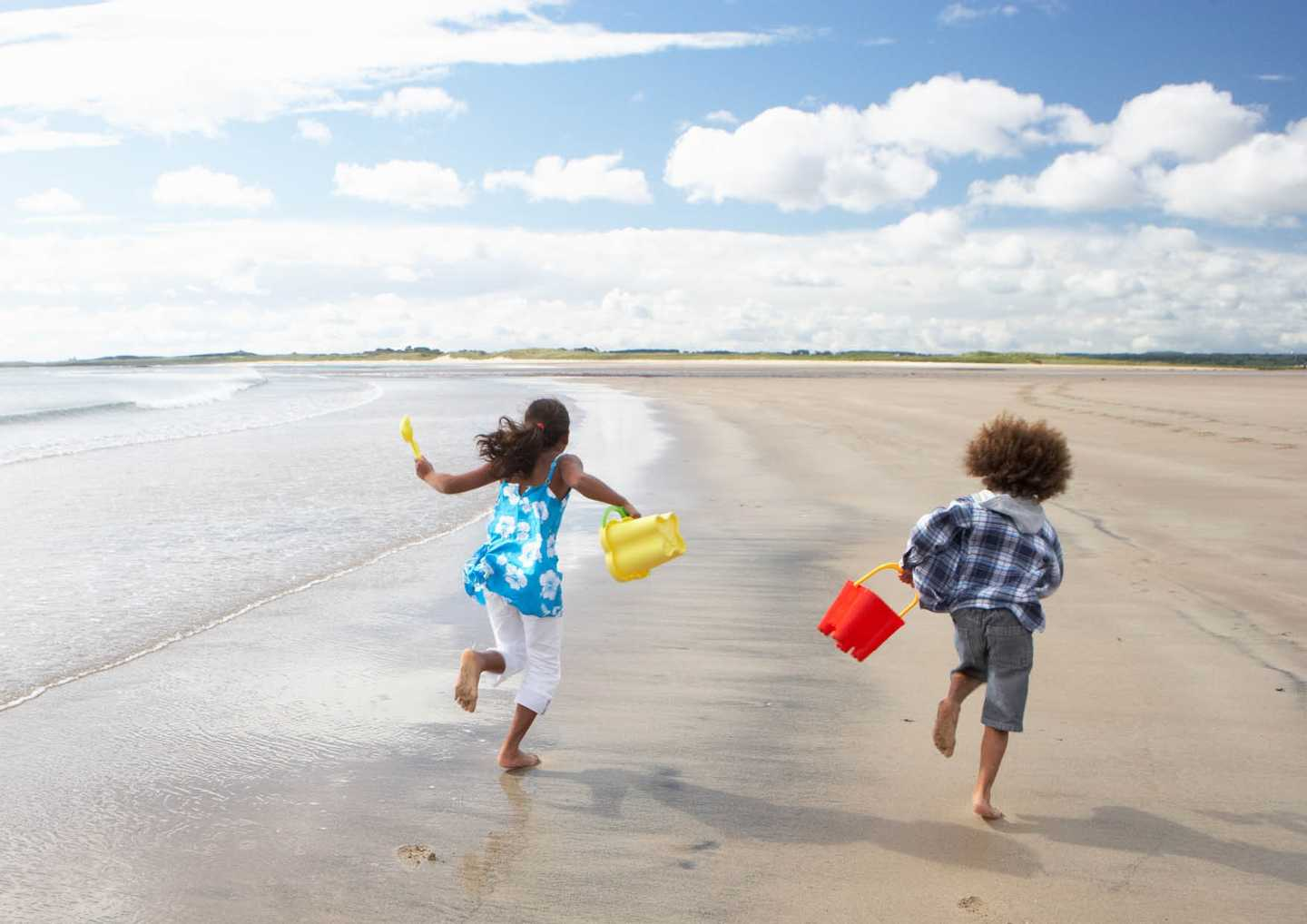 A brother and sister running a long the beach with buckets