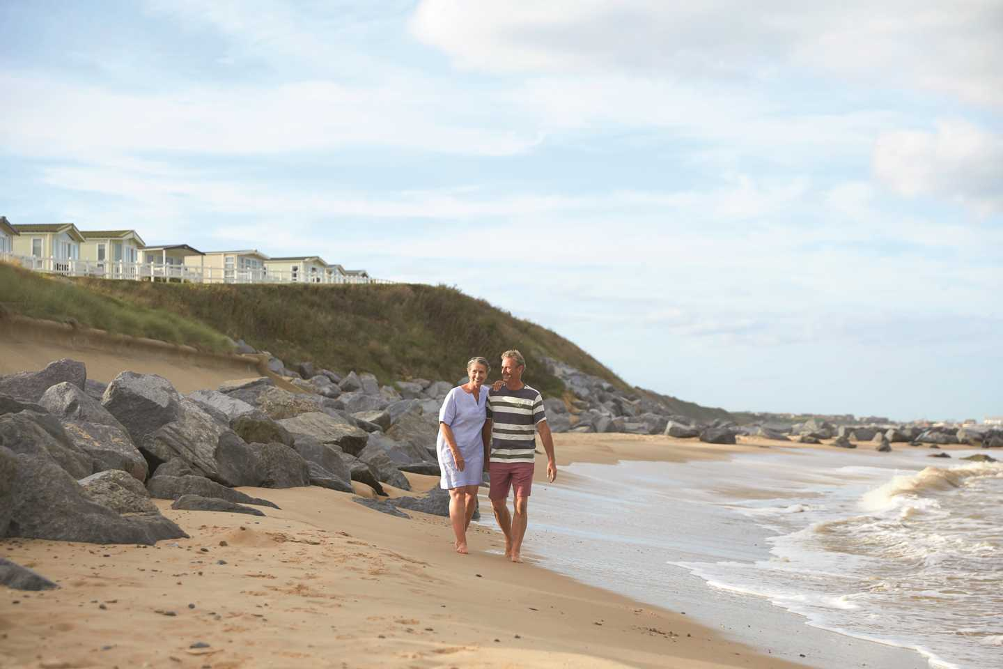 Couple walking on the beach at Hopton