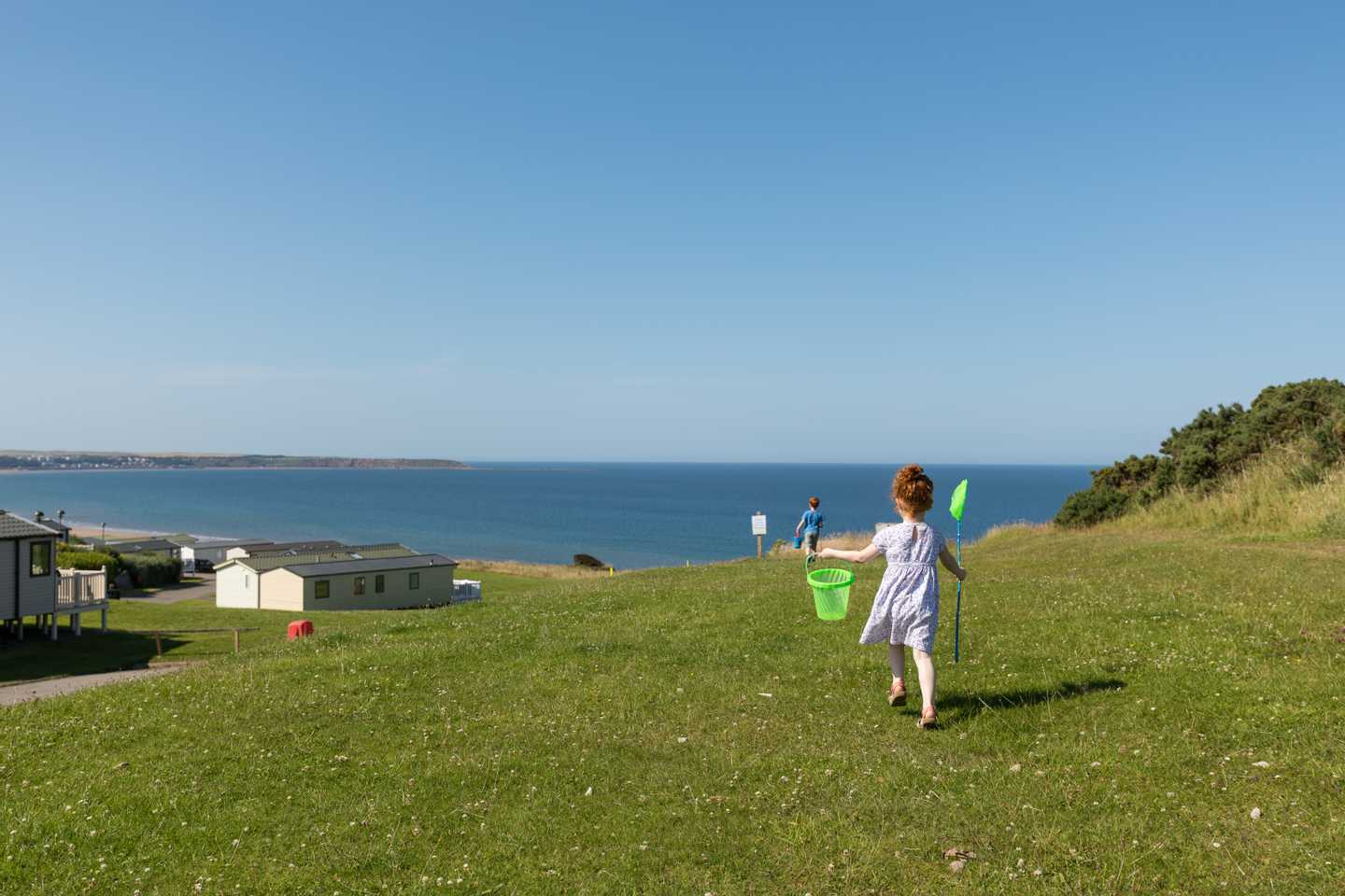 A little boy and girl walking along a hill with a bucket and spade as they make their way down to the beach on a day with clear blue skies
