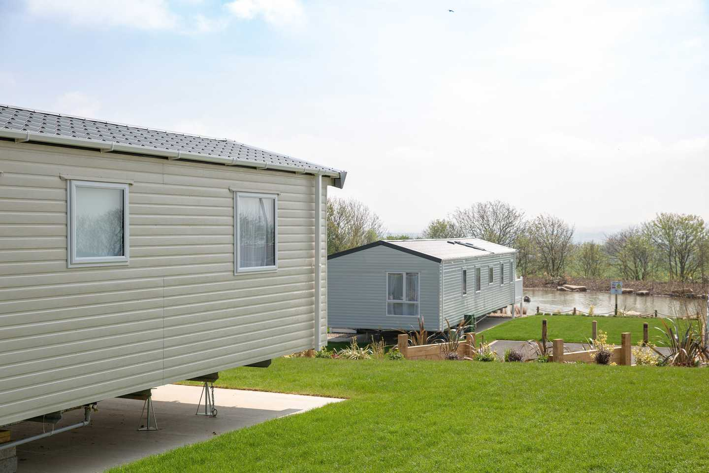 View of two Deluxe caravans and pond in background