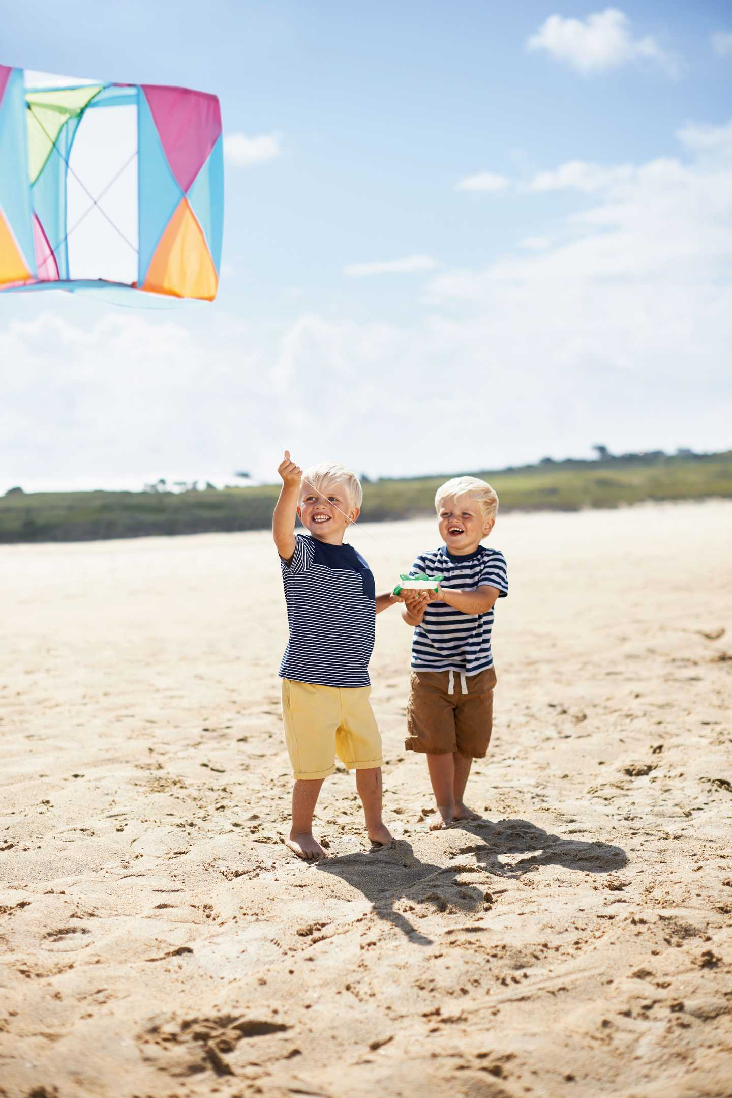 Children playing on the beach flying a kite