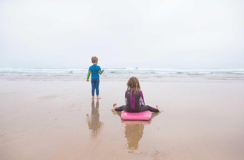 Children bodyboarding on the beach
