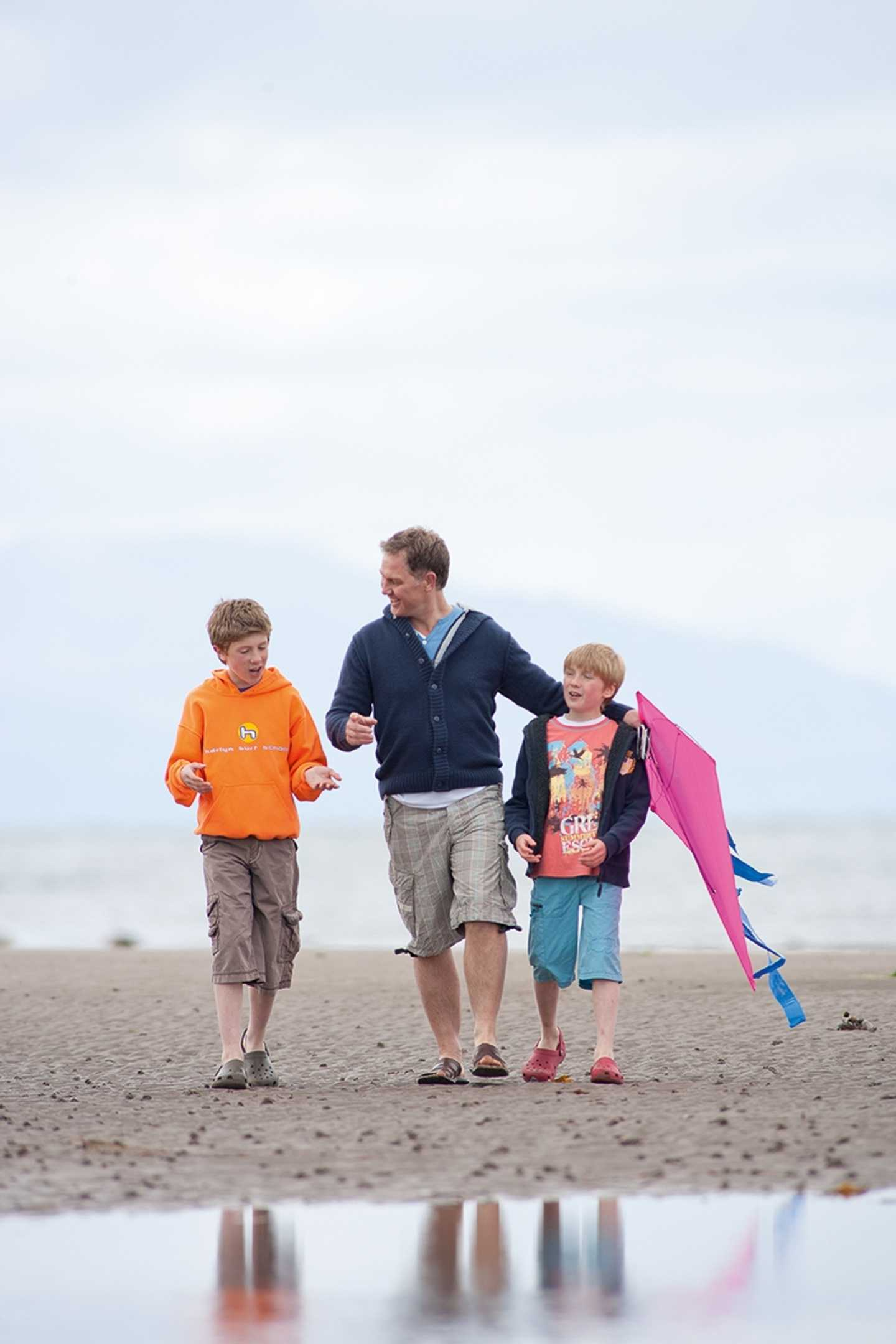 Parent and children flying kites on a beach by Craig Tara, Scotland