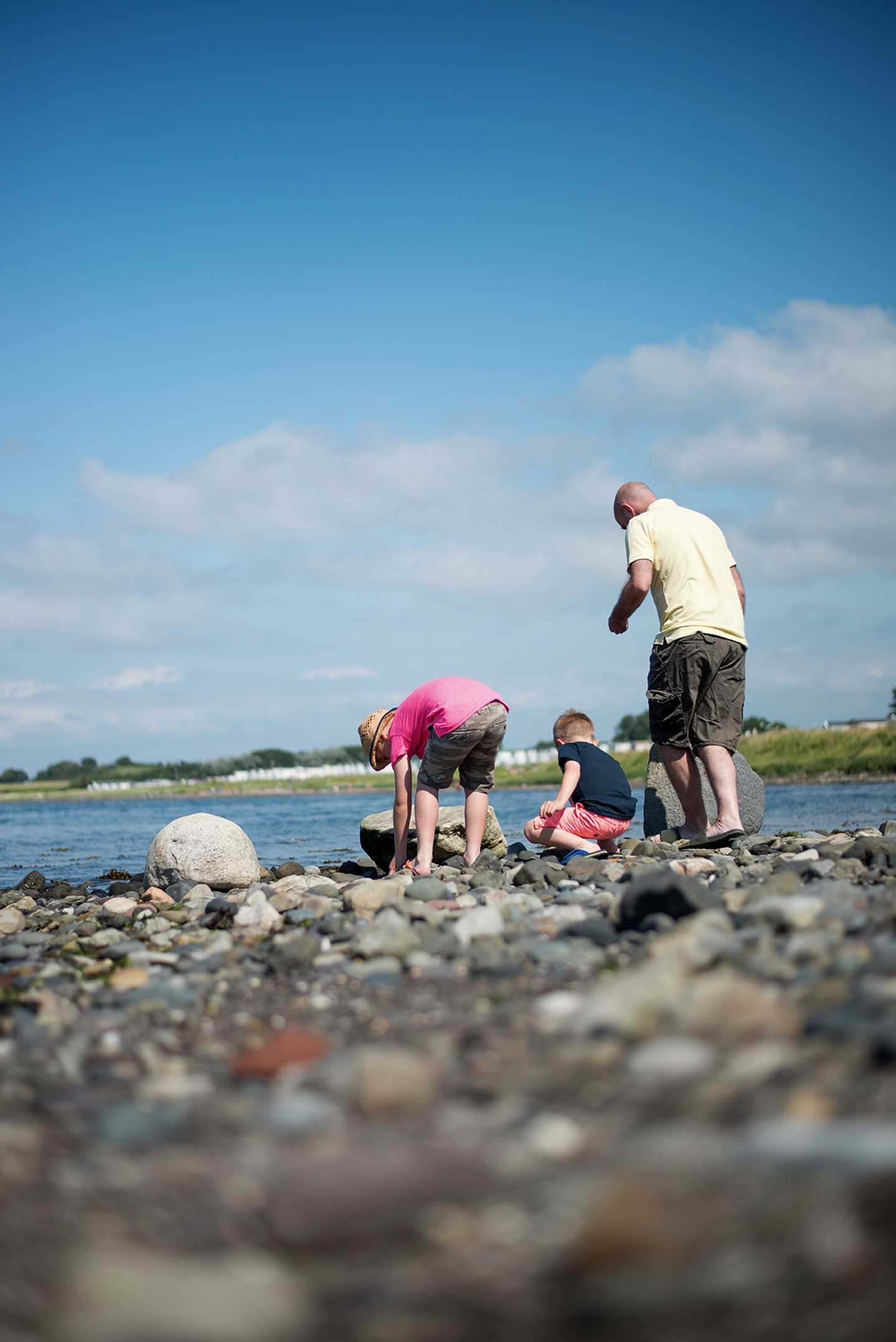A family playing on a stone beach