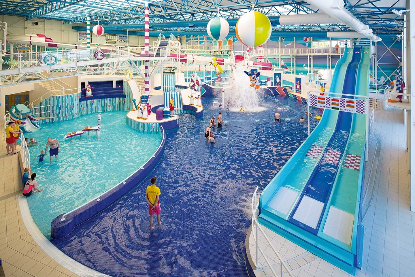 Guests splashing about in the heated indoor pool featuring slides and toddler zone