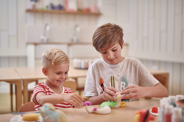 Two children being creative in the Creative Studio at Play Village at Craig Tara