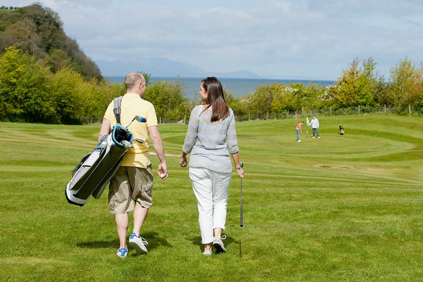 Couple playing golf over-looking the sea