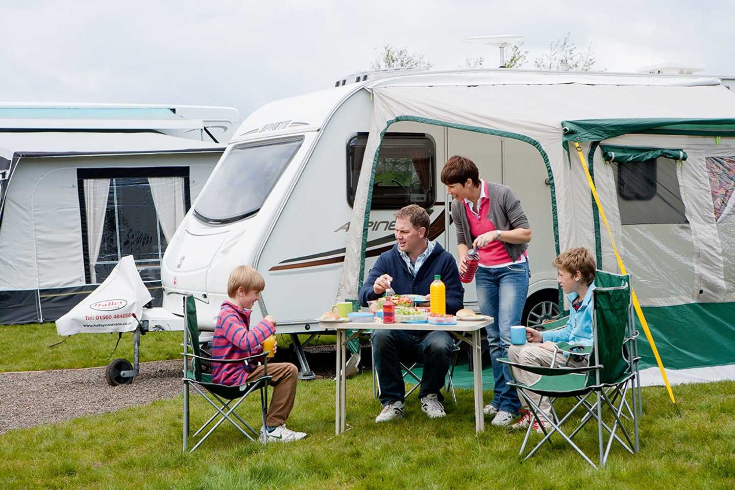 Family having food outside their caravan on the touring area at Craig Tara, Scotland
