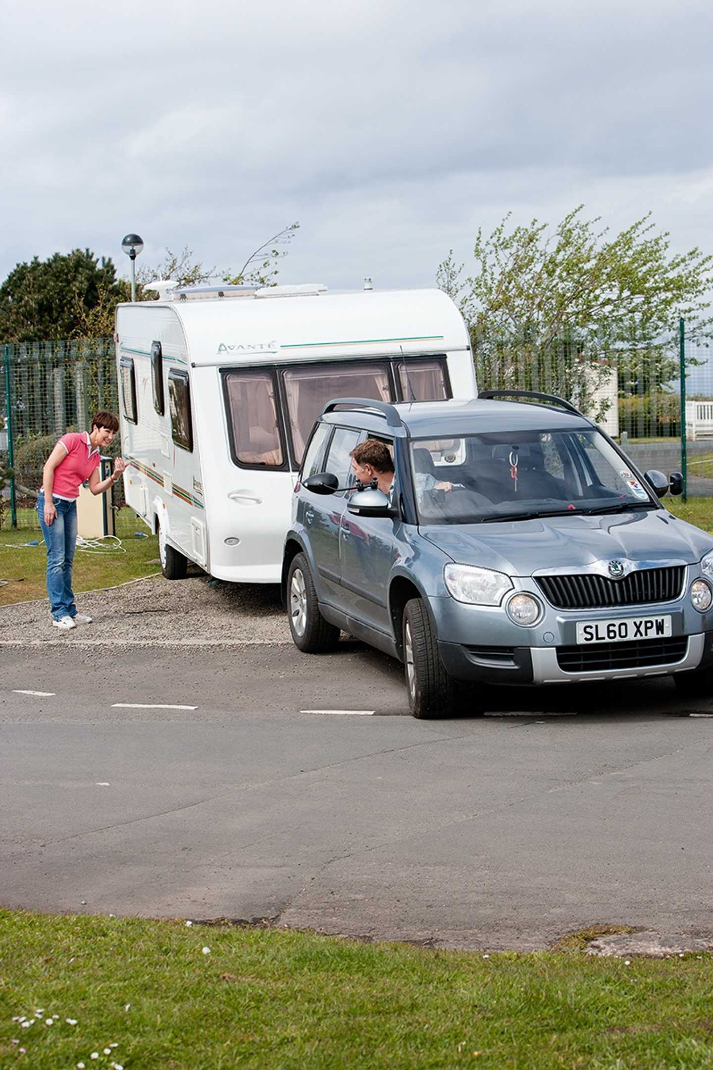 A car with a tourer attached reversing into a pitch