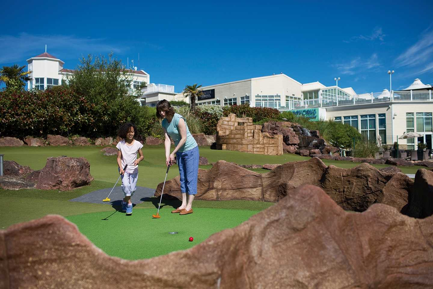 Family playing at the adventure golf course at Devon Cliffs
