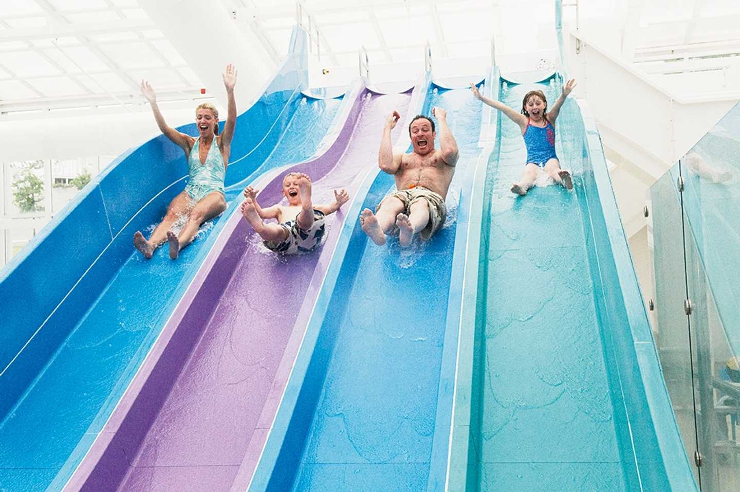 Guests whizzing down the indoor waterslide at Devon Cliffs
