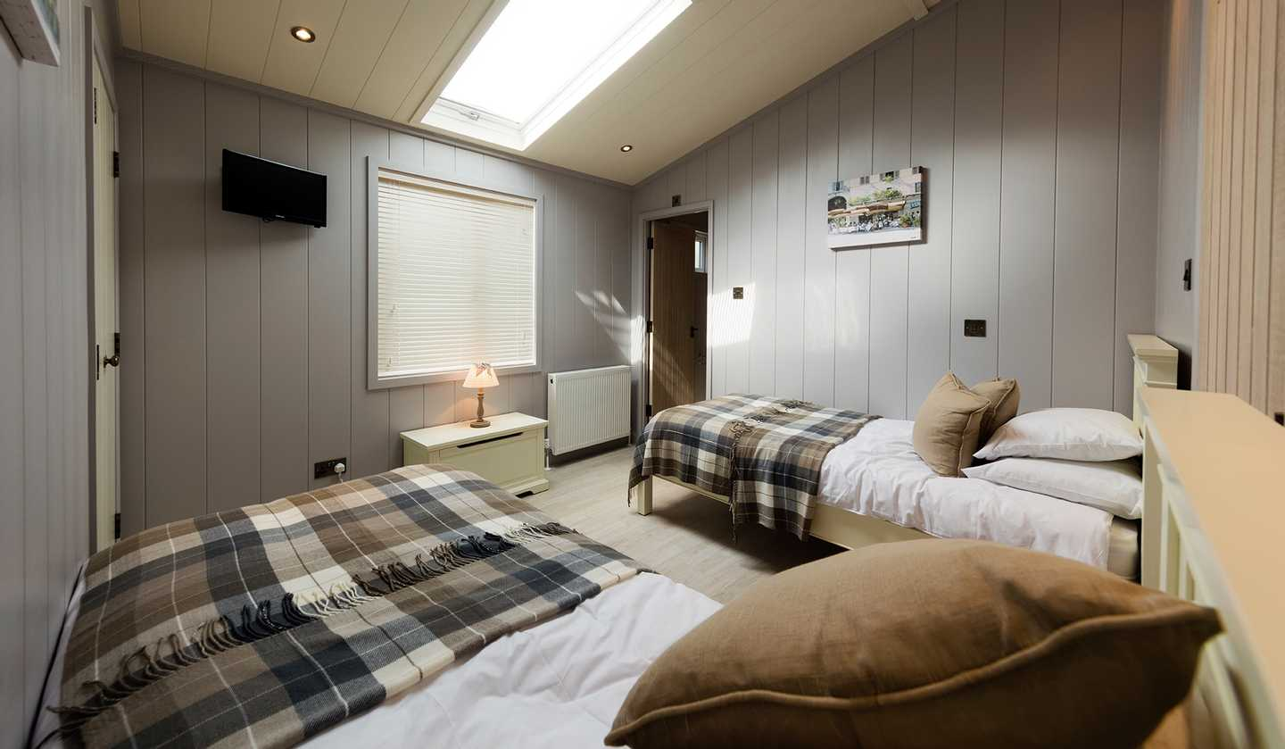 A Luxury Lodge twin bedroom with two single beds, TV, radiator and sky light