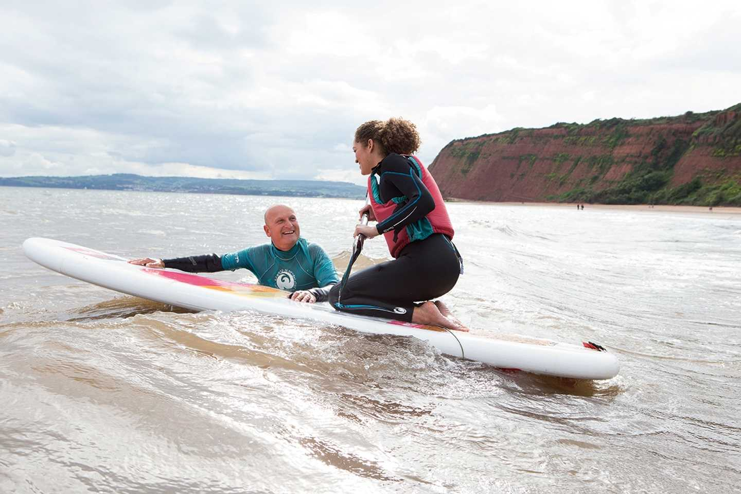 A guest paddleboarding in the sea in Devon