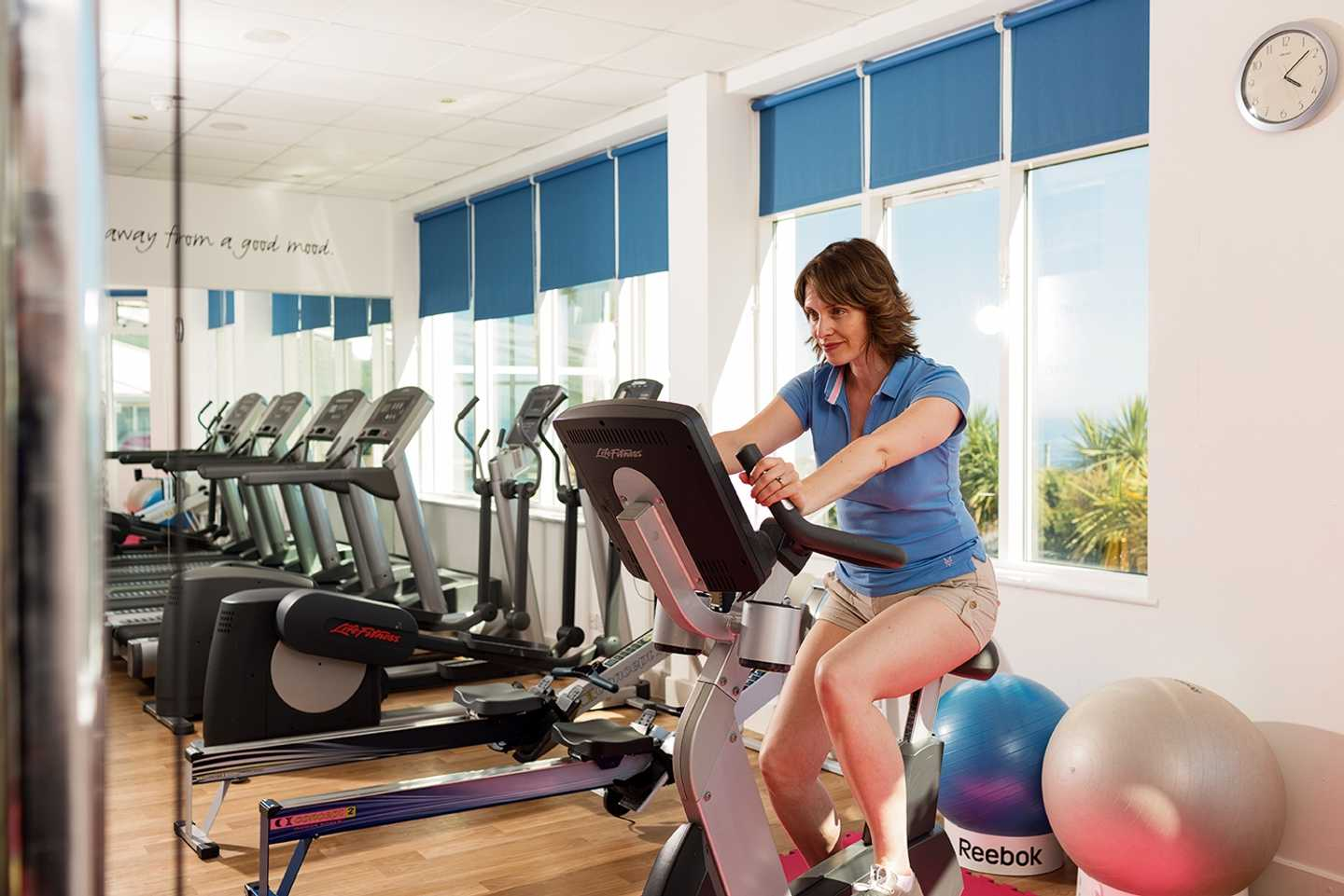 A lady using the exercise bike in our owners' gym