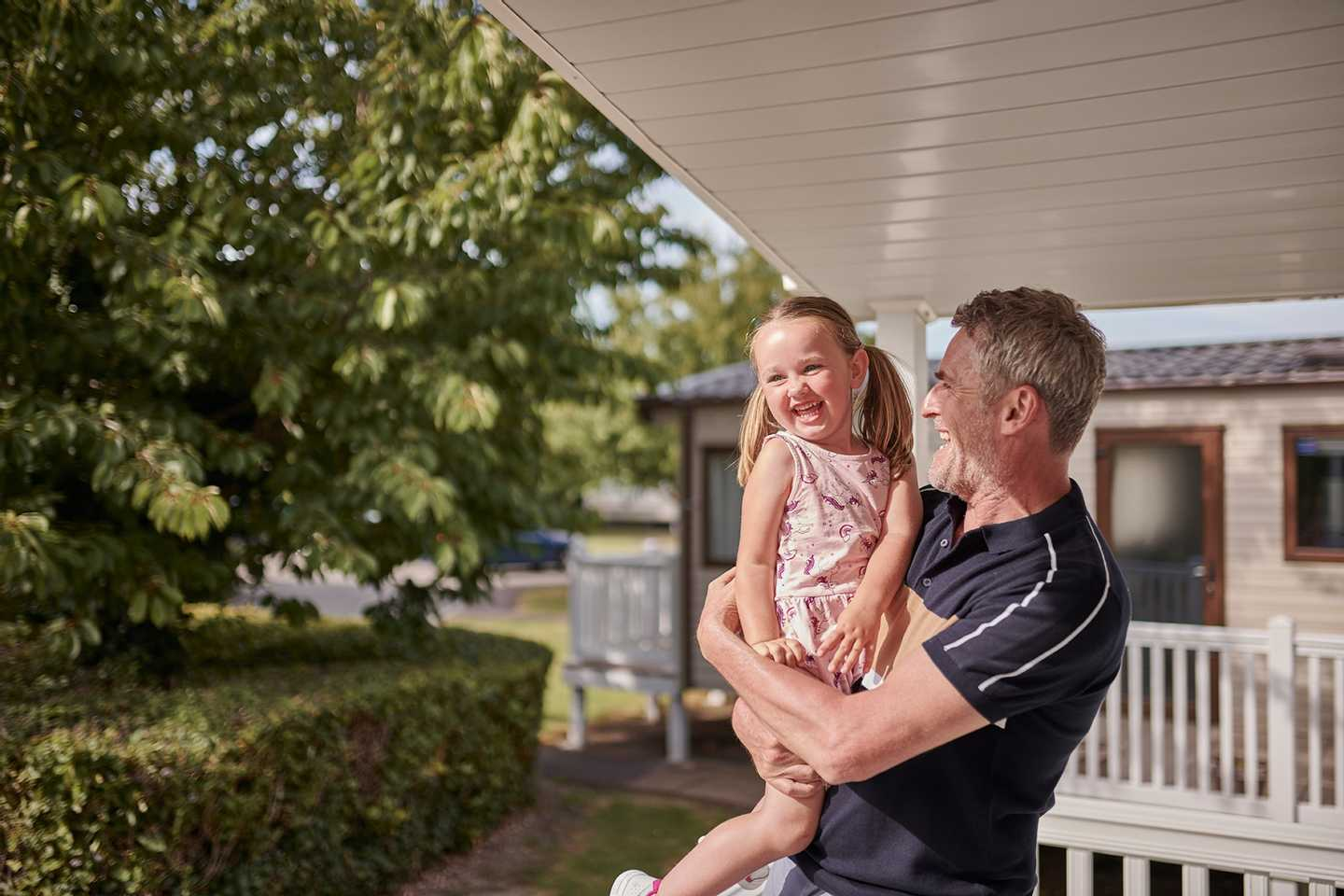 Father and daughter on the veranda of a caravan