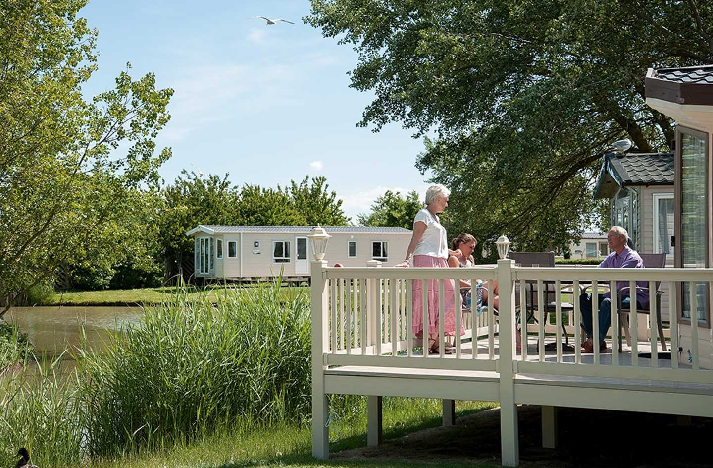 A family sitting on their veranda overlooking the lake at Burnham-on-Sea