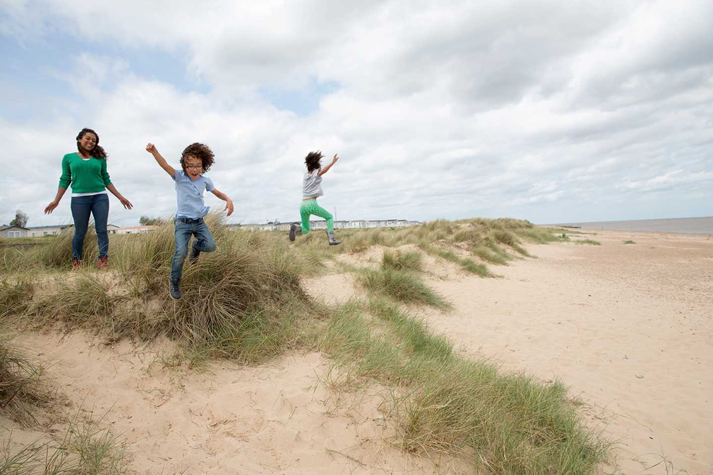 Family playing in the sand dunes at Seashore
