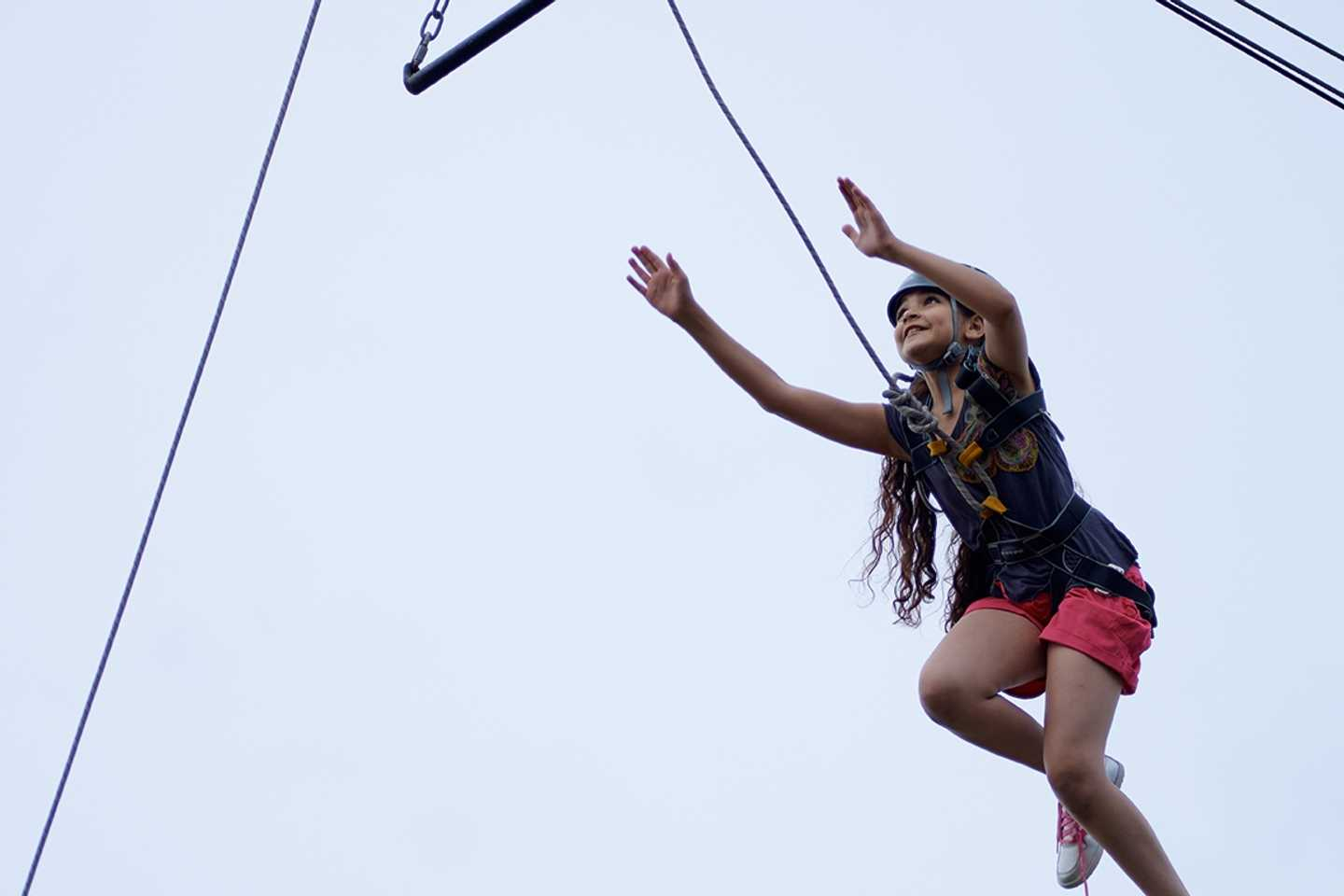 Child trying out the leap of faith in a harness