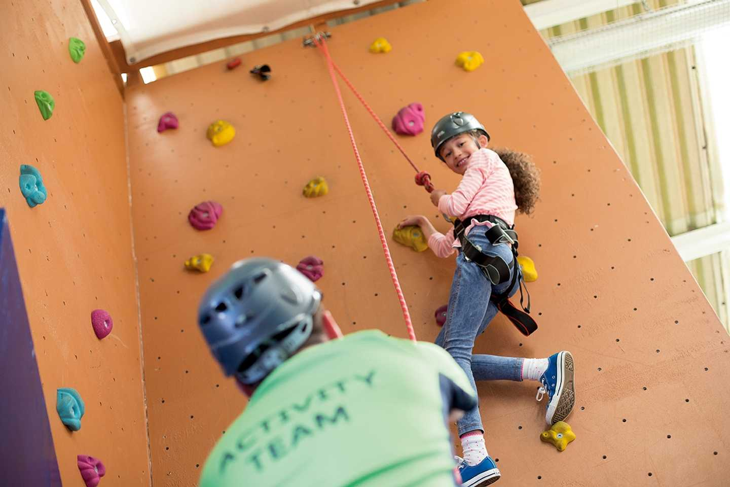 A child climbing up the climbing wall at Blue Dolphin