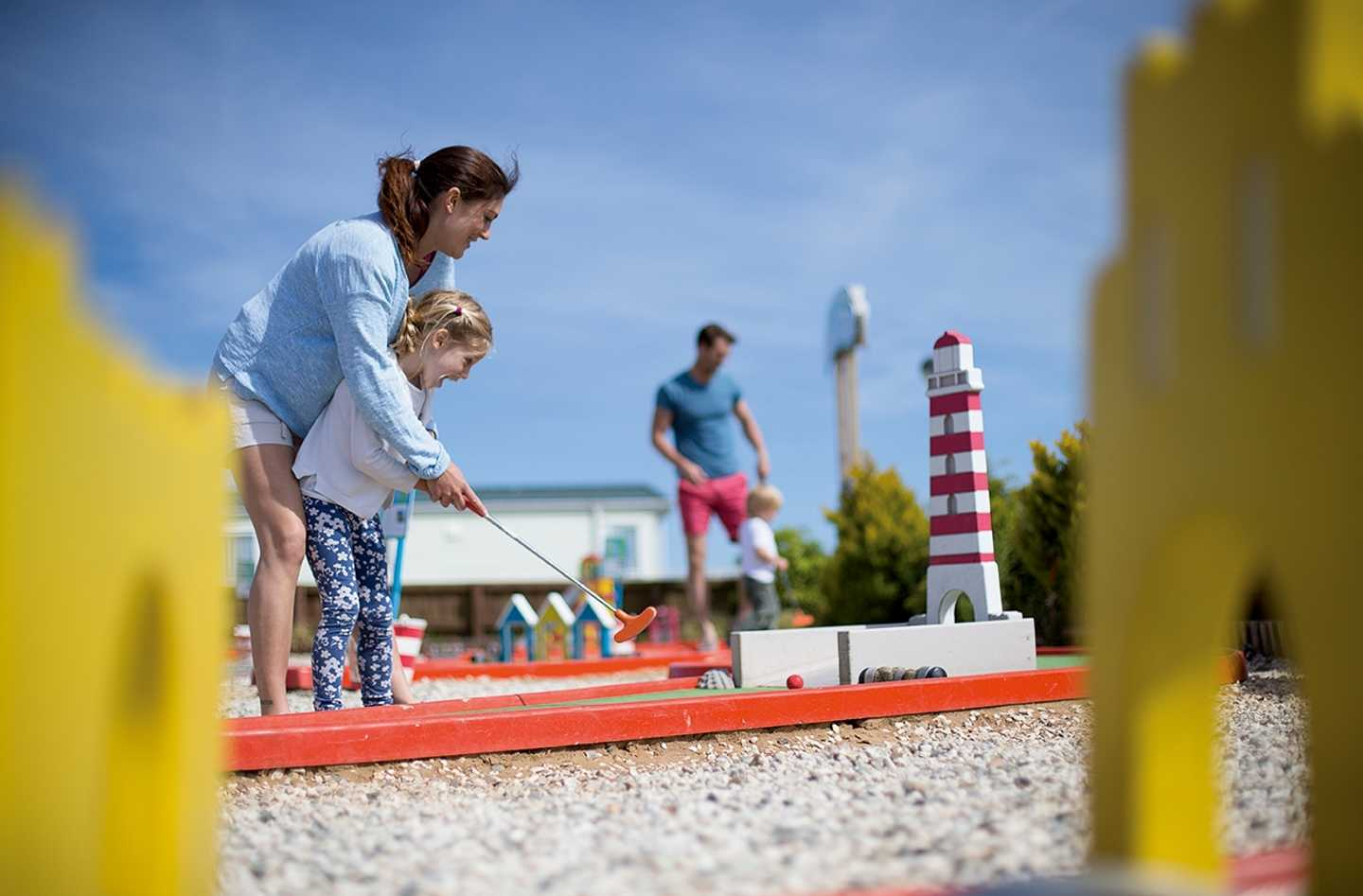A mother and child playing crazy golf