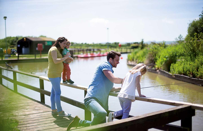 Family fishing on the bridge over the fishing lake