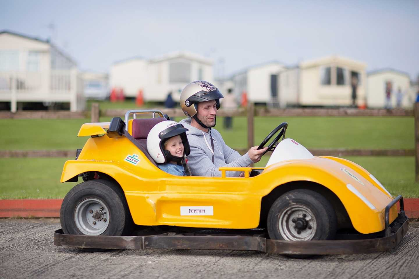 A father and son driving a go-kart