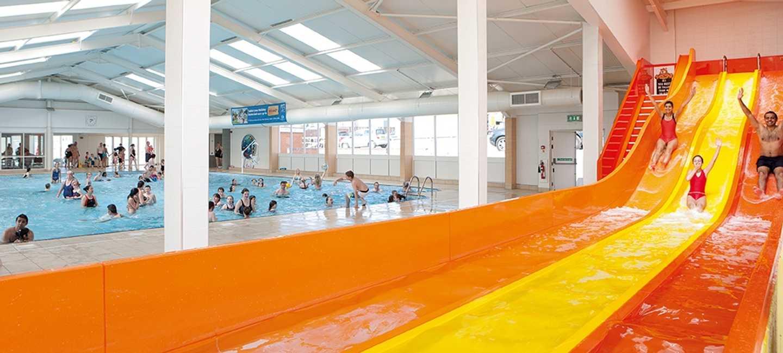 Guests sliding down the indoor pool slide