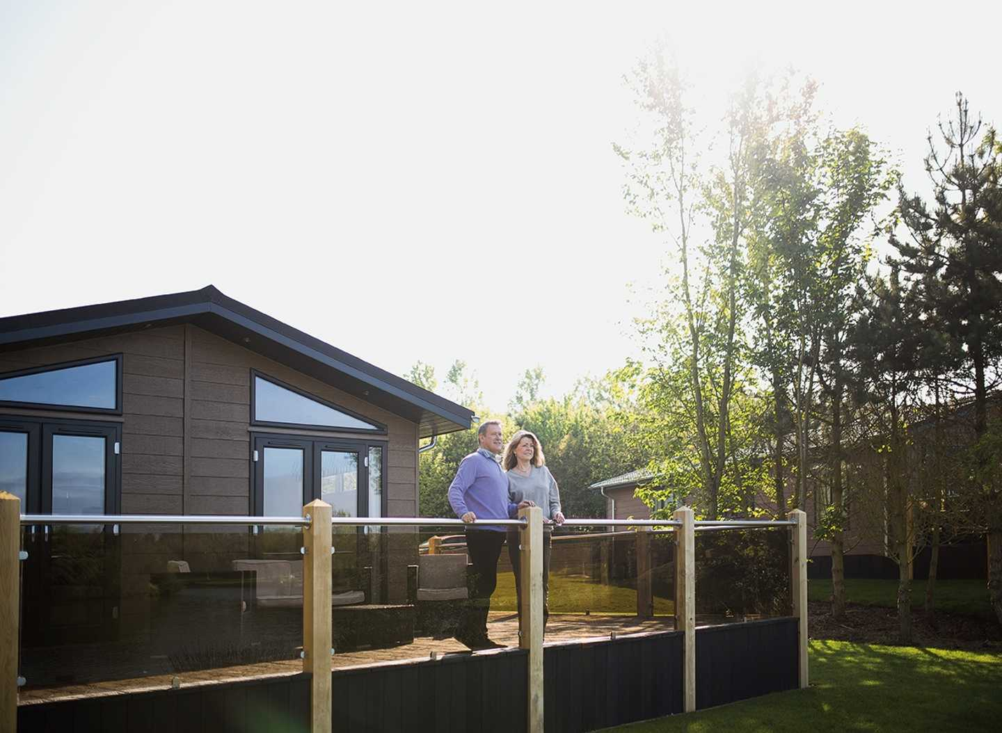 A couple standing out on a Luxury Lodge veranda