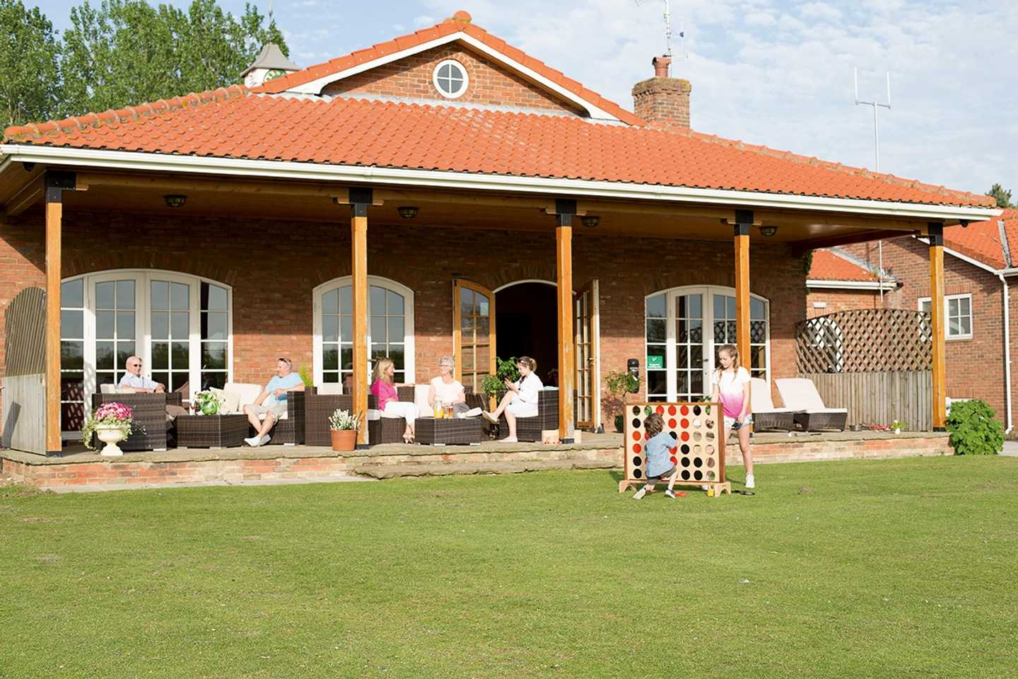Families sitting on the terrace of the Owners' Lounge and children playing giant Connect 4 on the grass